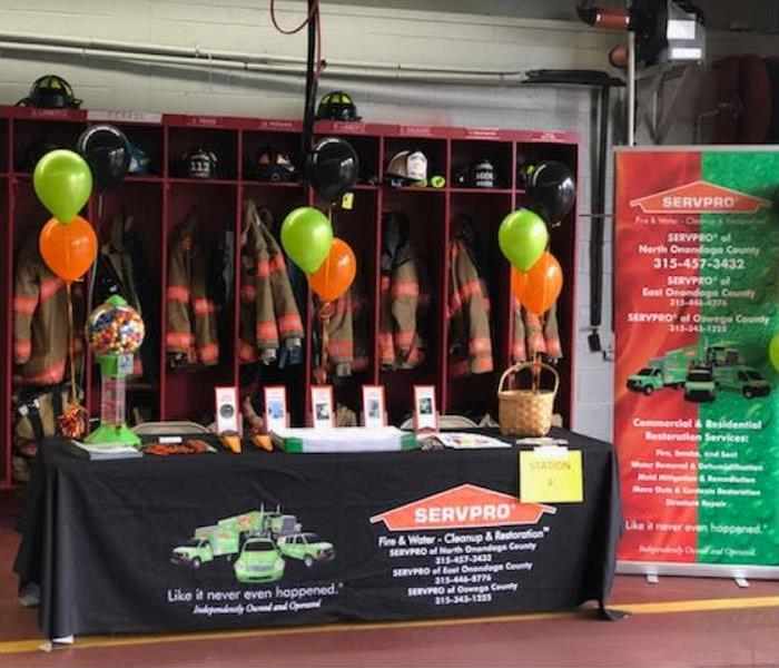 table with SERVPRO display set up in front of lockers holding each fireman's gear